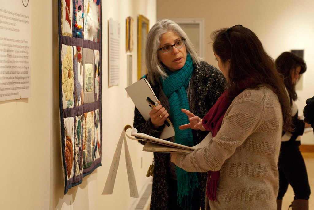 Professor Claudia Fieo working with one of her printmaking students in Wheaton's Beard & Weil Galleries