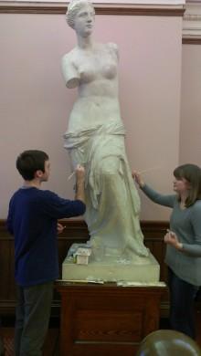 "Sarah Hilton ('16) and Jack Brotherton ('17) clean the plaster""Venus di Milo"" in Mary Lyon Hall"