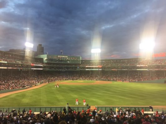 Cloudy skies, bright lights and a grassy baseball field with people below