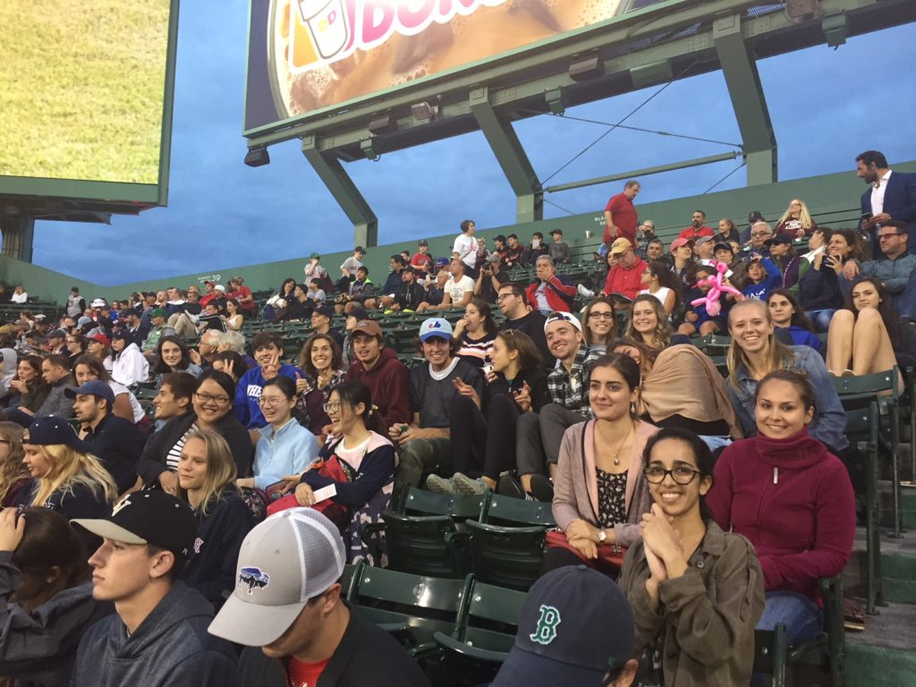 People sitting in bleacher seats while smiling and looking at the camera