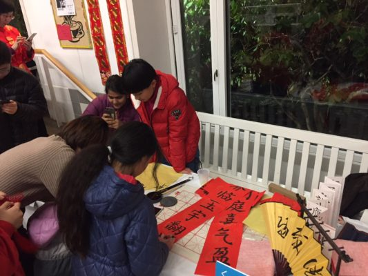 Several people are practicing Chinese calligraphy on a table with many different leafs of paper