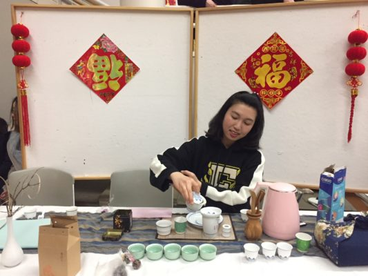 A photo of a student preparing and making tea at a table.