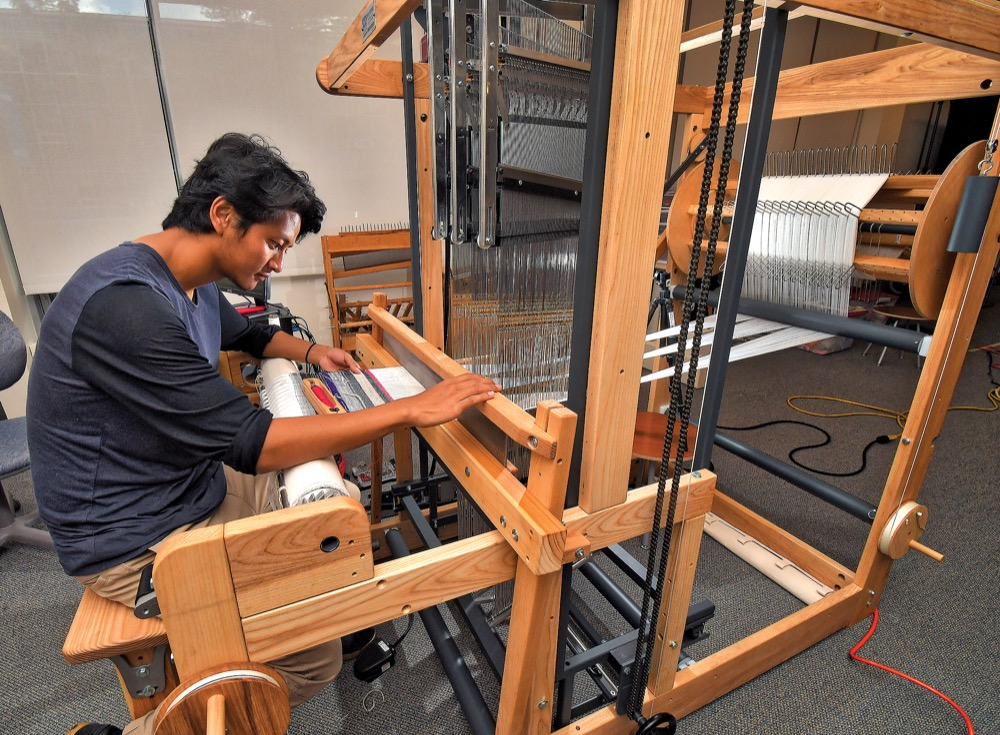 A student works with the college's new Jacquard loom