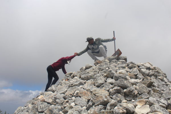 A photo of two people helping each other climb up a rocky mountain