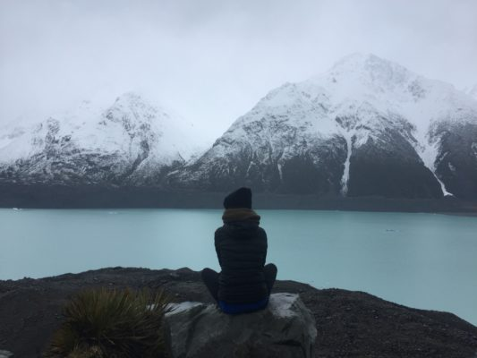 A photo of a woman sitting on a rock next to a lake with mountains in the background