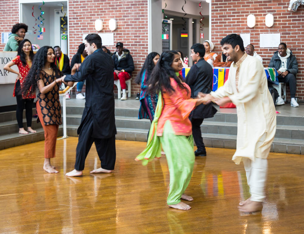 Photo of students in traditional clothing doing a Bollywood dance on a wooden floor with spectators watching