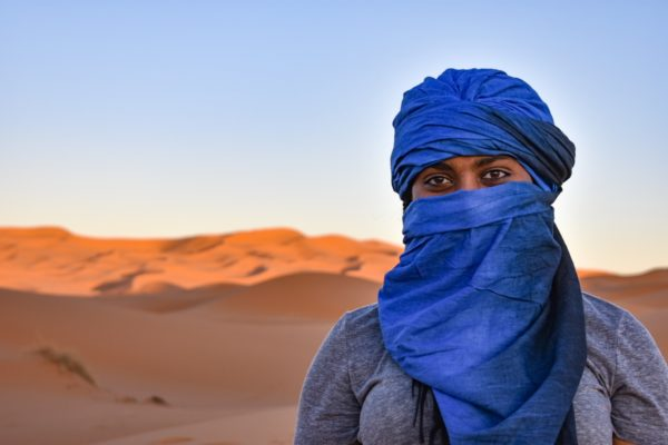 There is a woman with a viel standing in front of the desert sand.