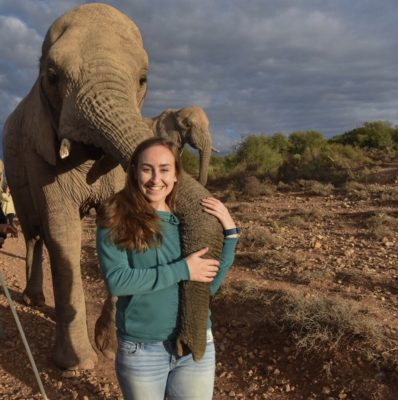 A woman is standing and posing in front of an elephant