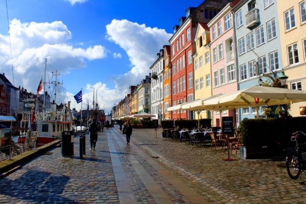 A photo of mulit-colored buildings, blue sky and a boardwalk. It is the classroom setting in Denmark