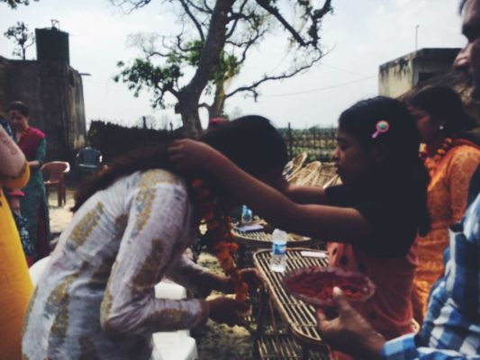 A photo of a woman placing a wreath around another woman while celebrating Holi
