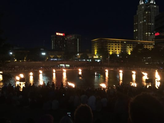 A photo of several firepits in the middle of a river in Providence. There are spectators sitting and standing nearby