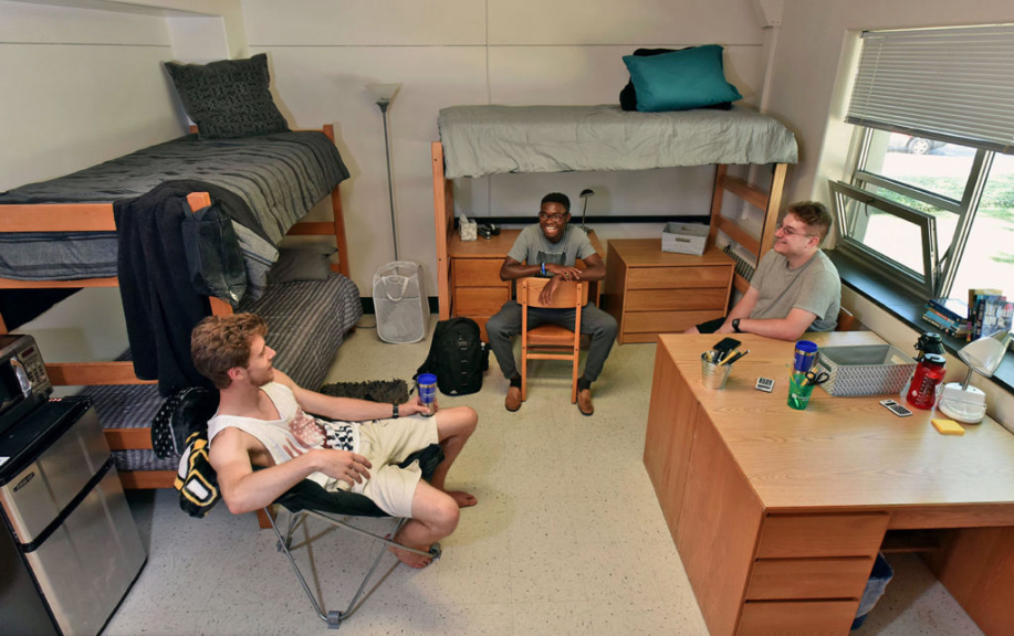 Here is a photo of a triple bedroom. There are two bunk beds with another bunk bed and a desk underneath it. There are three people sitting around in chairs in a circle.