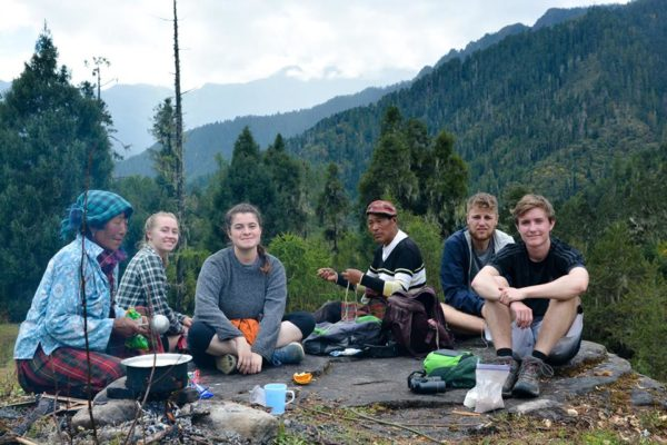 A group photo of students sitting in front of a campfire drinking tea in the mountains of Bhutan