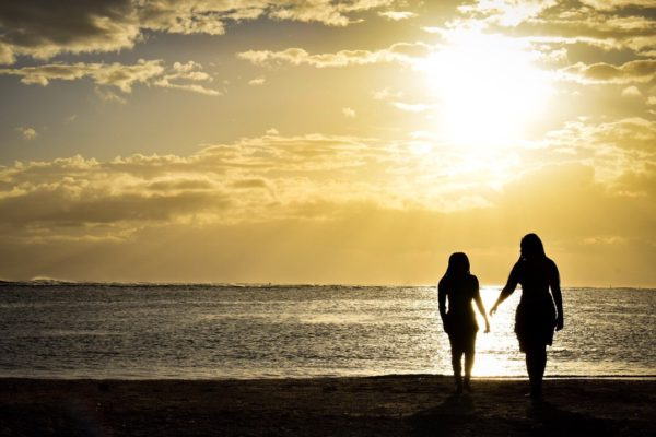 a photo of two people walking into a sunset on a beach in Hawaii