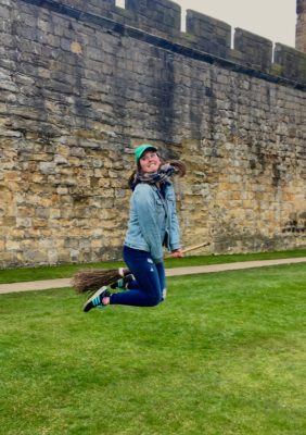 a photo of a woman jumping in the air on a broom. She is standing on grass with a castle wall behind her.