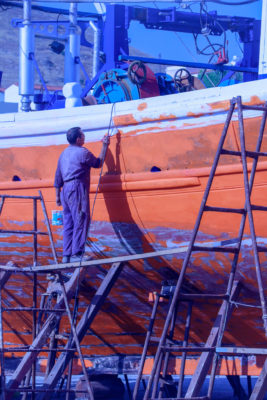 A photo of a man standing on scaffolding while painting a boat red