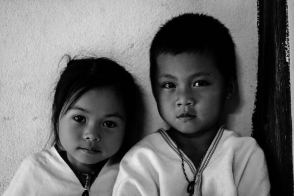 A black and white photo of two children staring at the camera