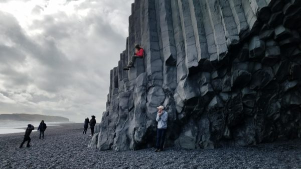 A group photo of people standing in front of a pillar in Iceland
