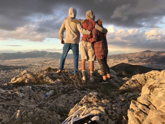 A group photo of people overlooking the city of Athens from a hill