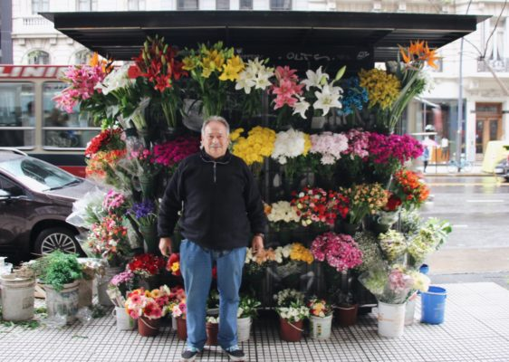 A photo of a man in front of different flowers.