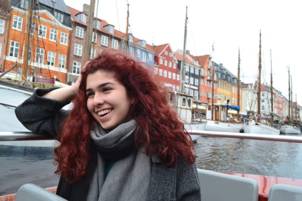 A photo of a woman with red hair smiling on a boat. There are multiple different colored houses behind her.