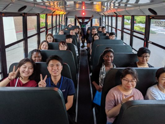 A group of students on a bus smiling and waving at the camera