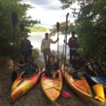 A group of students posing for a photo with paddles and kayaks