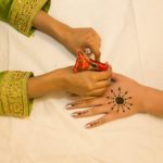 A photo of a person drawing henna on someone's hand