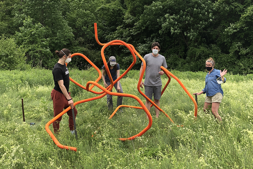 Professor Kelly Goff and group install sculpture on nature trail